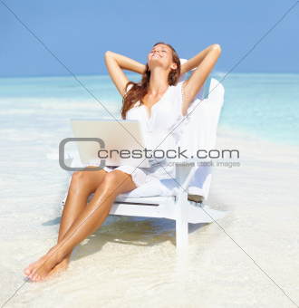 Relaxed woman with laptop on beach