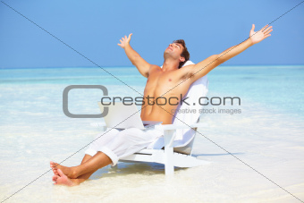 Peaceful man with laptop on beach
