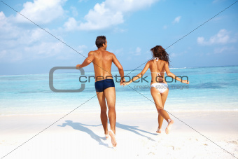 Couple running together on beach