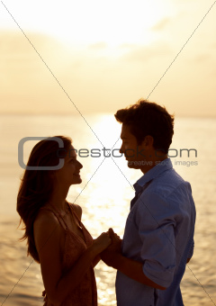 Young couple on the beach holding hands at sunset