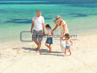 Beautiful family walking along sandy beach