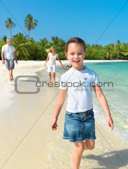 Cute girl walking on the beach with her family in background