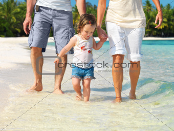 Adorable little girl with her parents at the beach