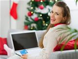 Smiling young woman making Christmas shopping on internet