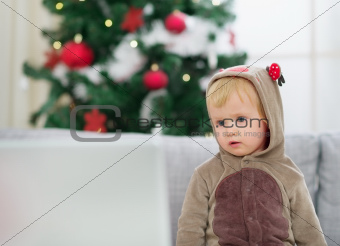 Thoughtful baby in deer suit near Christmas tree looking in laptop