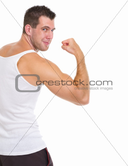 Happy male athlete showing biceps
