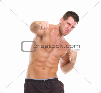 Angry muscular sports man punching