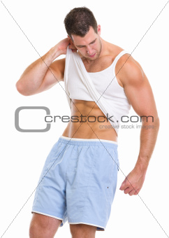 Man raising shirt to show abdominal muscles