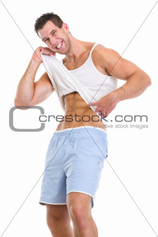 Happy man pointing on abdominal muscles