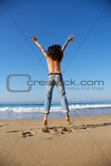 back of woman jumping at seashore
