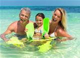 Portrait of smiling family of three in sea water with fins