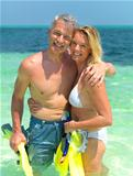 Romantic couple with snorkeling gear standing in sea water