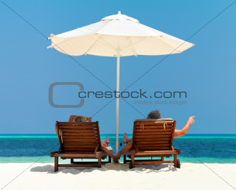 Couple on deck chairs relaxing on the beach