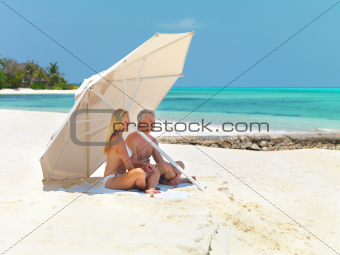Mature couple on beach under umbrella