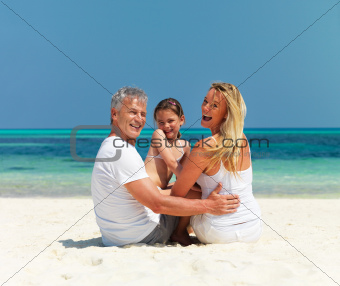 Beautiful family sitting on the beach