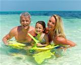 Happy family in ocean water with snorkeling gear