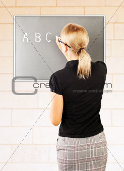 Young teacher write on blackboard