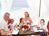 Beautiful family enjoying beach dinner