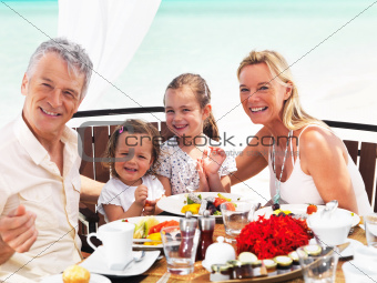 Happy family having exotic beach dinner