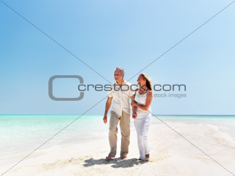 Happy mature couple enjoying beach holidays