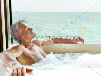 Mature man relaxing in bathtub with a galss of champagne