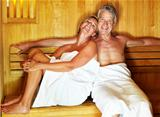Happy middle aged couple enjoying a hot sauna