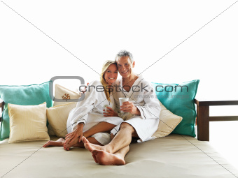 Romantic mature couple having coffee on bed
