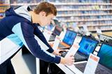 Young man in consumer electronic store looks at laptop