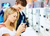 Young couple checking out new digital camera at store