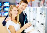 Young couple in electronics shop with digital camera
