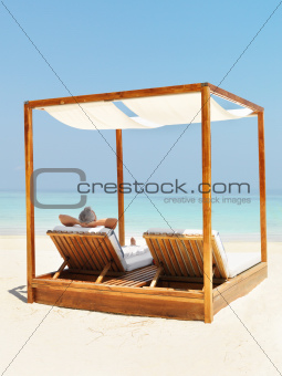 Man relaxing on a deck chair by the beach