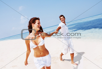 Happy couple at the beach in a playful mood