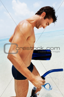 Young man on the beach with snorkeling equipments