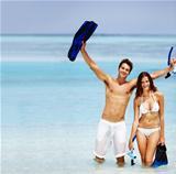 Portrait of a happy couple at the beach with snorkeling gear in a playful mood