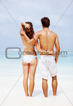 Romantic young couple standing together on the beach