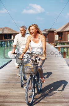 Happy mature couple enjoying cycle ride