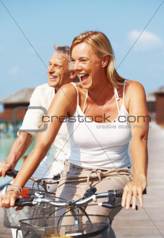 Cheerful middle aged couple having fun on holidays riding bikes outdoors
