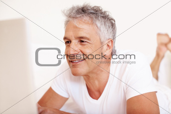 Senior man using a laptop on bed