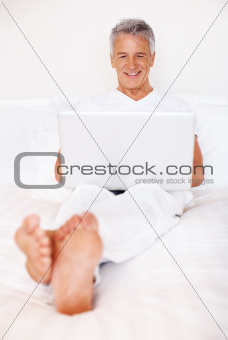 Mature man browsing internet on laptop in bed