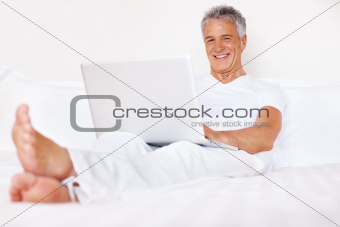 Handsome caucasian man sitting in bed with laptop