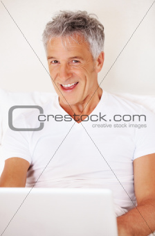 Joyous mature man in bed with laptop