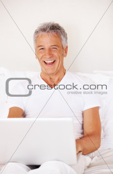 Cheerful middle aged guy on bed with a laptop