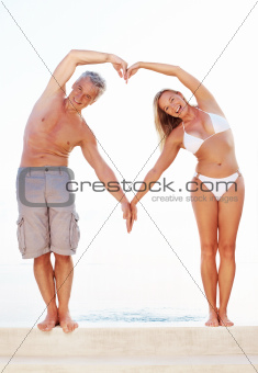 Mature couple making heart shape with arms