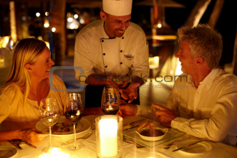 Senior couple at restaurant talking to waiter