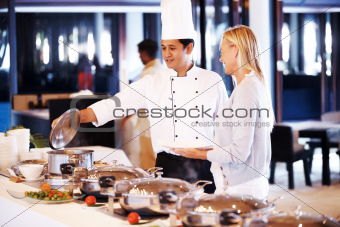 Helpful chef serving food to pretty mature woman