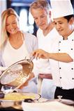 Happy cook serving food to mature couple