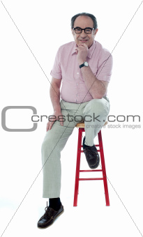 Confident senior man resting on stool
