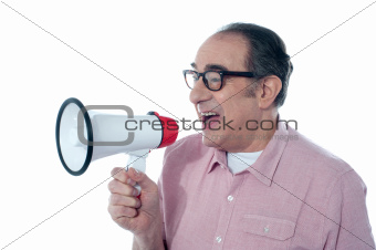 Elder casual man shouting through megaphone