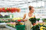 Copyspace- attractive young ethnic woman standing in nursery surrounded by flowers with basket of flowers holding flower pot with blurred background