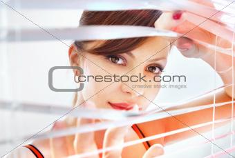 woman looks through jalousie